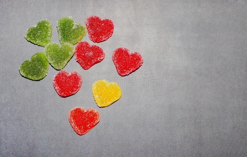 Multicolored marmalade sweets in the shape of a heart on a dark blackboard background. Marmalade multi-colored sweets, isolate. Mine Space, Valentine`s Day stock photography