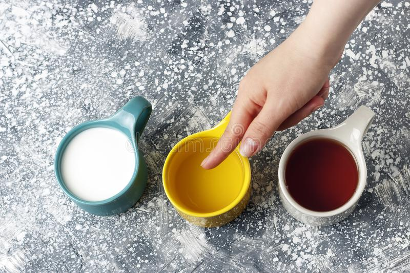 Multicolored mugs with drinks and female hand on a gray background, top view stock images