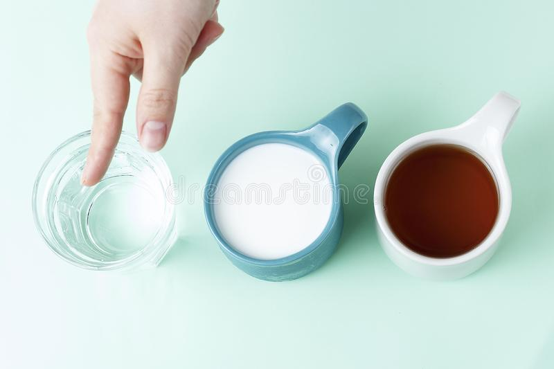 Multicolored mugs with hot drinks and female hand on a blue background, top view stock photos