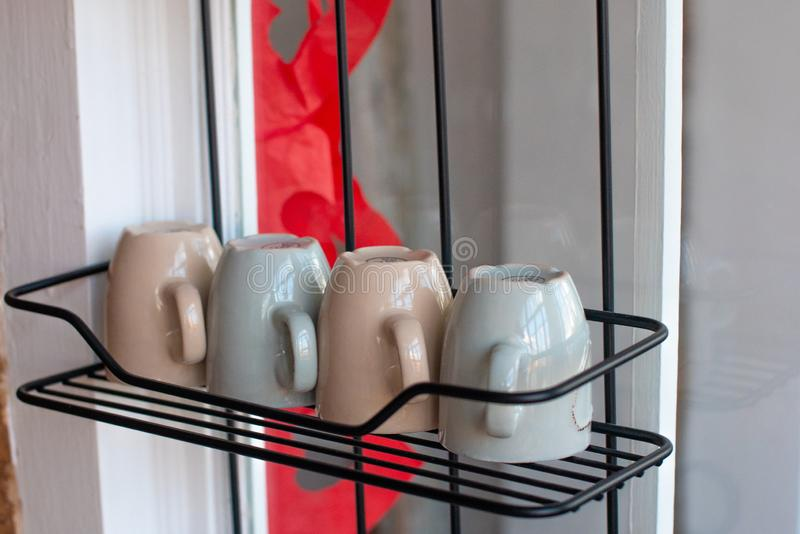 Multicolored mugs on a stand stock image