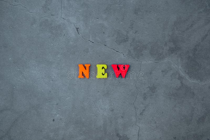 The multicolored new word is made of wooden letters on a grey plastered wall background stock photos