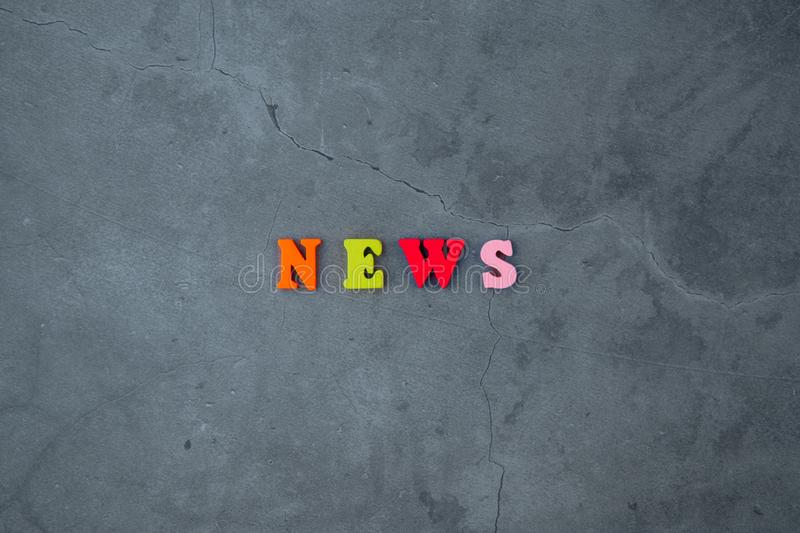 The multicolored news word is made of wooden letters on a grey plastered wall background.  stock images