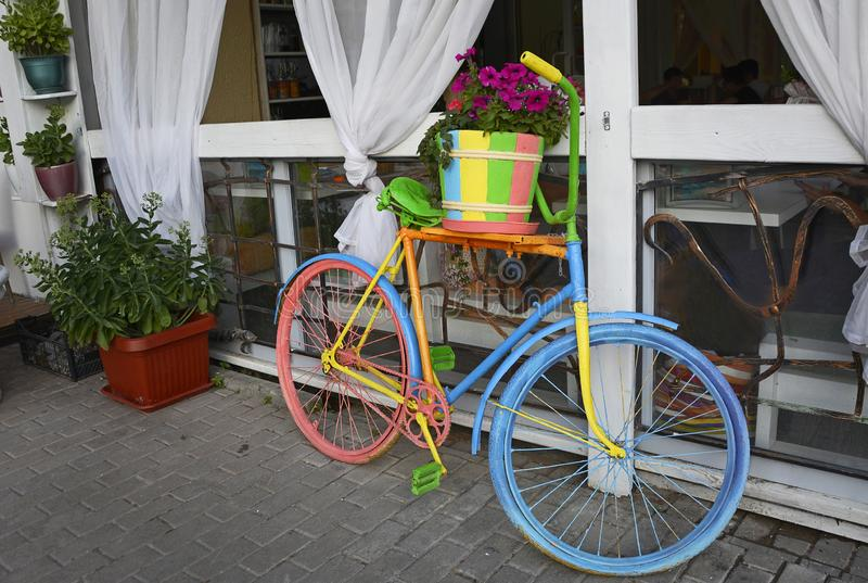 Multicolored old bicycle with a flower pot, summer decoration. Close up royalty free stock photo