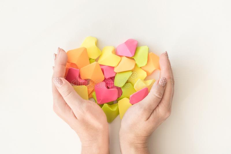 Multicolored origami paper hearts in female hands. Women hands holding many bright heart. Love, romance, dating royalty free stock image