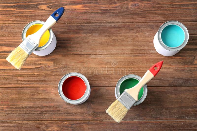 Multicolored paint in tin cans on wooden background stock photos