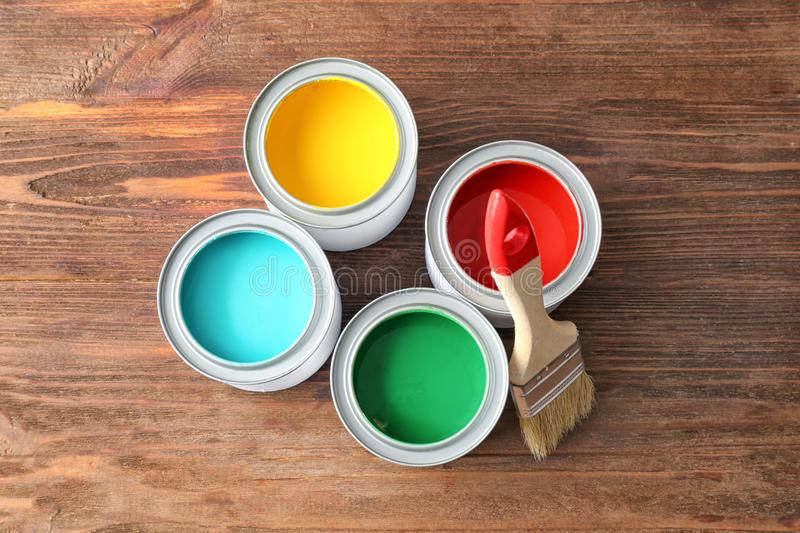 Multicolored paint in tin cans on wooden background, royalty free stock photo