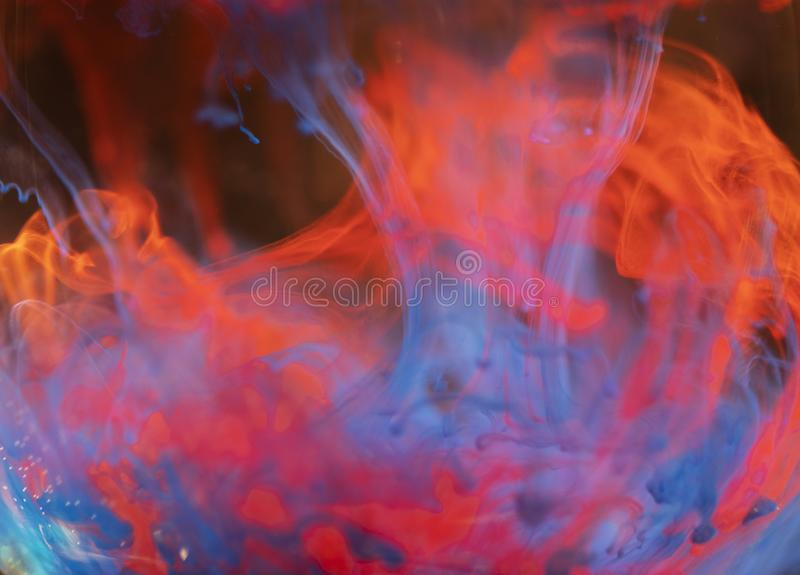 Multicolored paint in the water close-up. Multicolored paint poured into a glass of water slowly dissolve and take a variety of patterns stock photo