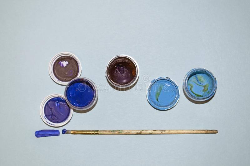 Multicolored paints in jars on a blue background. Materials for drawing stock image