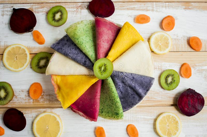 Multicolored pancakes lined on plate in a circle and decorated with pieces of beetroot, lemon, carrot, kiwis, stock photo