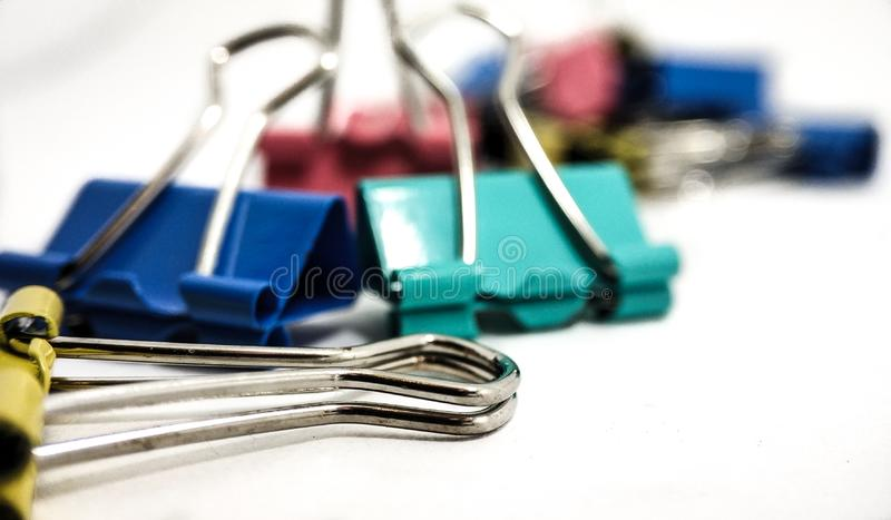 Multicolored paper clips in a pile close up on a white background royalty free stock images