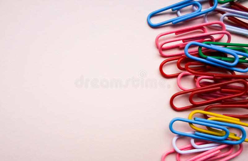 Multicolored paper clips on a pink background. The concept is time to school. Multicolored paperclips on a pink background royalty free stock photos
