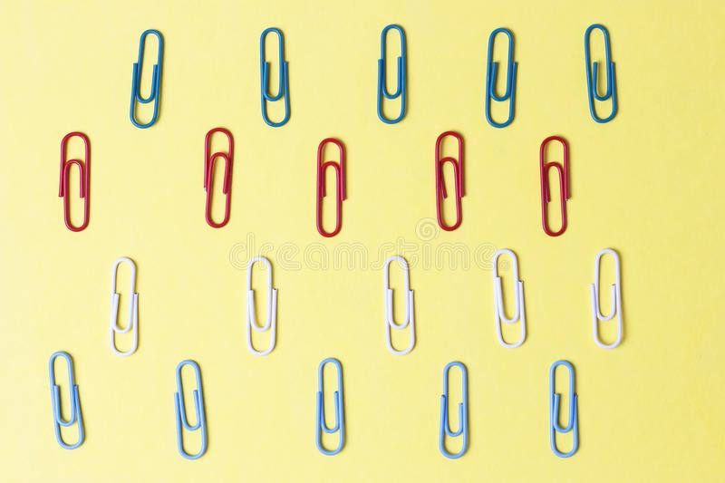 Multicolored paper clips on a yellow background, office concept. A multicolored paper clips on a yellow background, office concept stock images