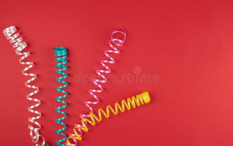 Multicolored paper serpentine on red paper, festive background. Copy space stock photos