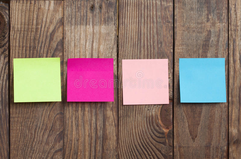 Multicolored paper stickers note on wooden stock photos