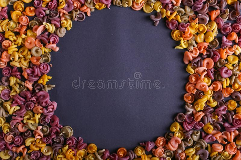 Multicolored pasta with the addition of natural vegetable dye. Scattered on a black background, copy space. Top view, pattern. Multicolored pasta with the stock photos
