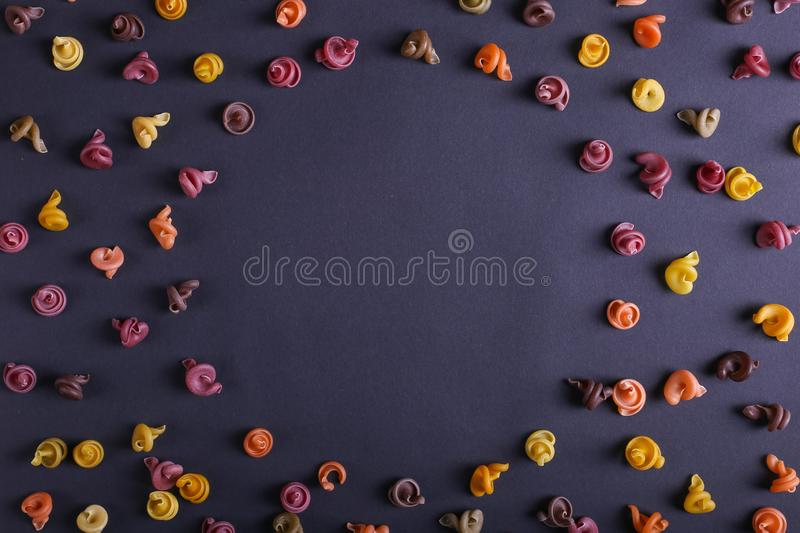 Multicolored pasta with the addition of natural vegetable dye. Scattered on a black background, copy space. Top view, pattern. Multicolored pasta with the stock images