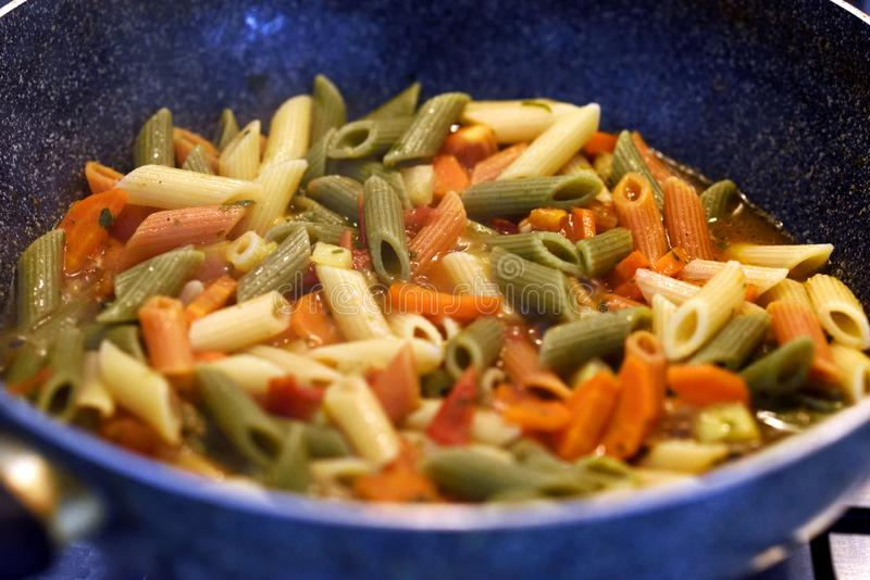 Multicolored pasta with vegetables. Close-up of  multicolored pasta with vegetables. Italian dish stock photography