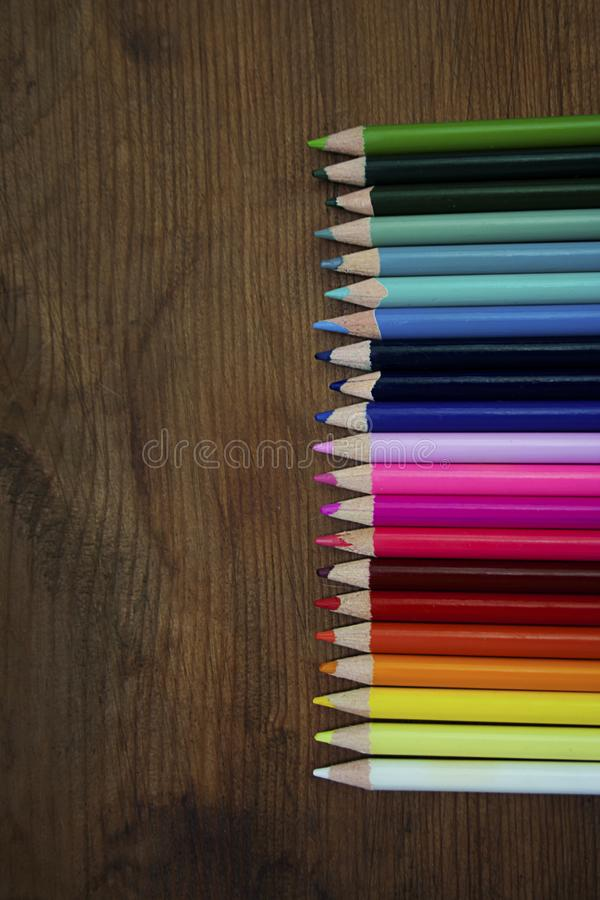Multicolored pencils against wooden background stock photos