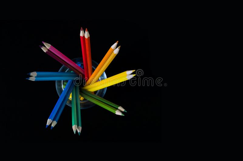 Multicolored pencils on a black background in the form of a heart, a place for an inscription stock photos