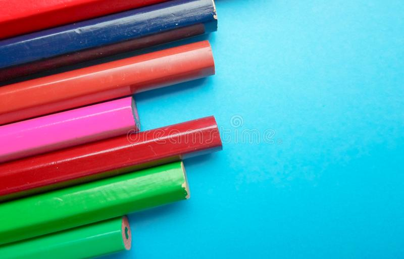 Multicolored pencils on a blue background. space for text. Multicolored pencils on a blue background stock photo