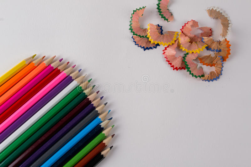 Multicolored pencils and pencil shaves on white background. Copy space stock image
