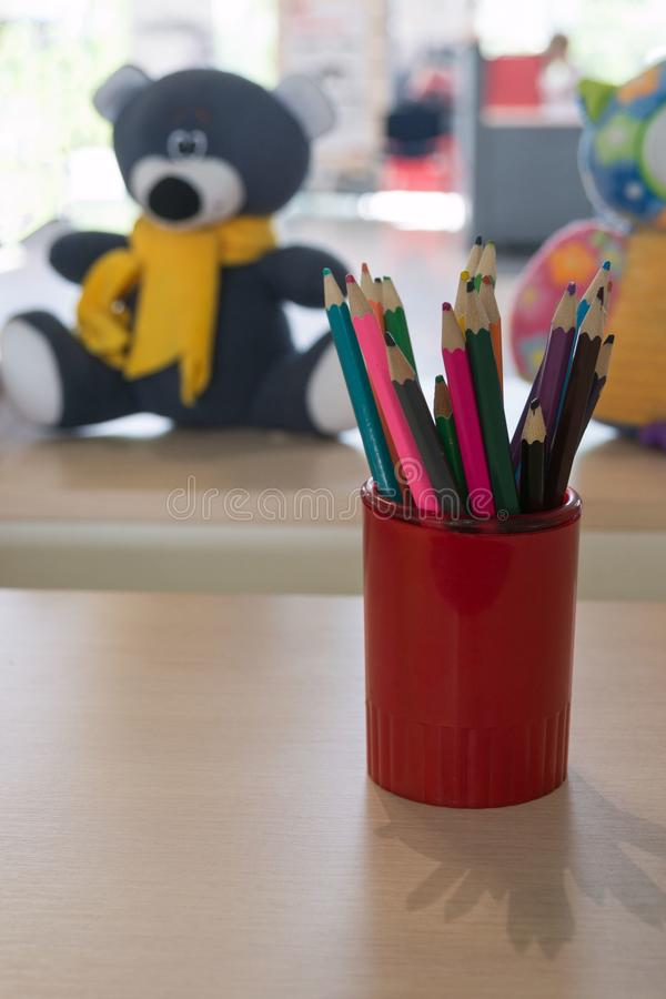 Multicolored pencils in a red cup on a wooden table. In the background - children`s toys. Children`s corner - a place for drawin stock images