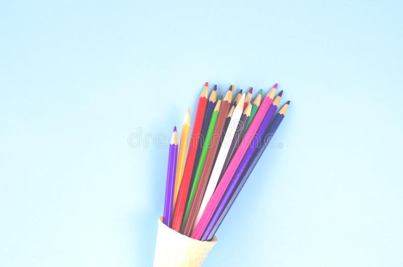 Multicolored pencils in a waffle cup of ice cream stock images
