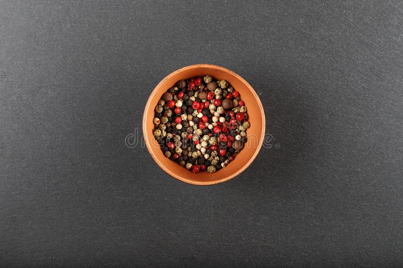 Multi-colored pepper on a black background. Multicolored pepper peas in a clay plate in the center on a black background, top view royalty free stock photos