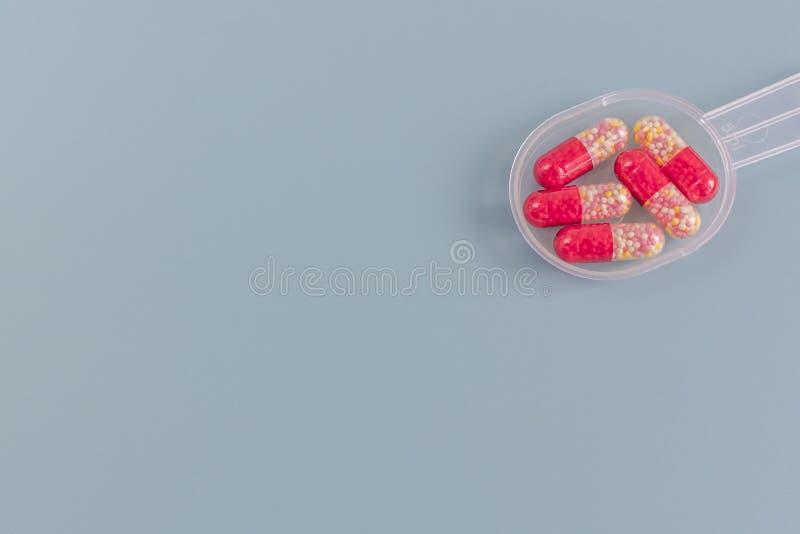 Multicolored pillen of capsules op een metende lepel op een blauwe achtergrond met exemplaarruimte royalty-vrije stock fotografie