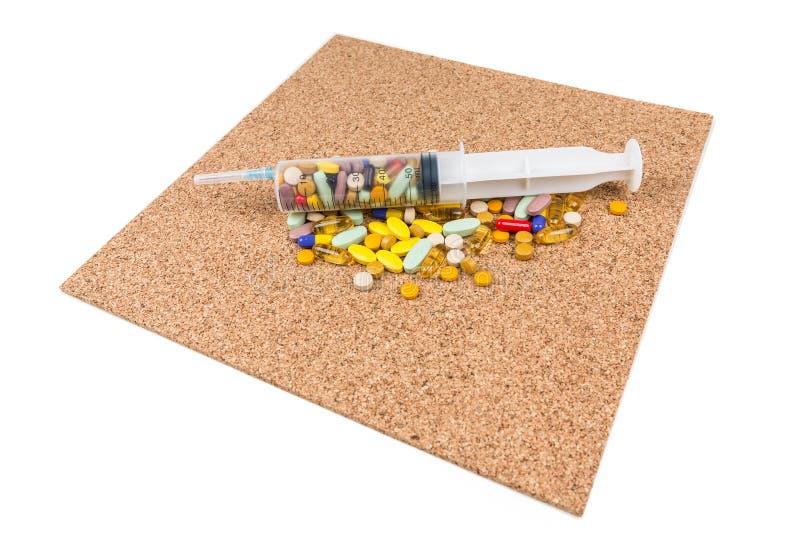 Multicolored pillen in een grote spuit over cork royalty-vrije stock afbeeldingen