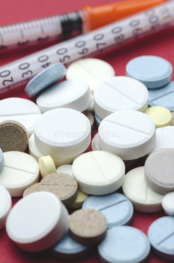 Multicolored pillen in het centrum en de spuit royalty-vrije stock afbeeldingen