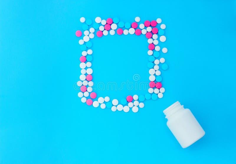 Multicolored pillen op blauwe achtergrond met exemplaarruimte royalty-vrije stock foto