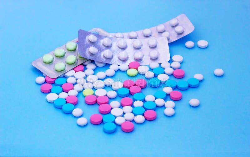 Multicolored pillen op blauwe achtergrond met exemplaarruimte stock afbeeldingen