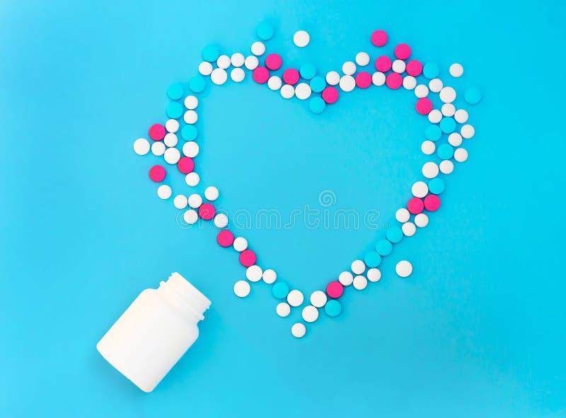 Multicolored pillen van witte kruiken op een blauwe achtergrond stock foto's