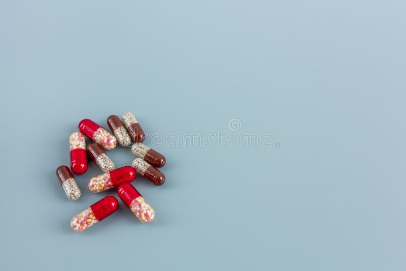 Multicolored pills or capsules on a blue background with copy space. Pharmaceutical drug, pain medicine, antibiotic  for the treatment of patient stock image