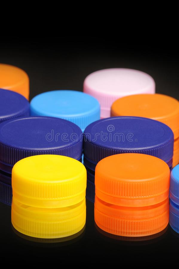 Stack of colorful plastic bottle caps on black royalty free stock photography