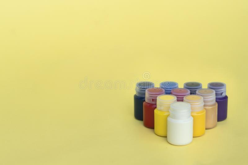 Multicolored plastic cans with acrylic paint on a yellow background. Art supplies. Set for the artist. royalty free stock photo