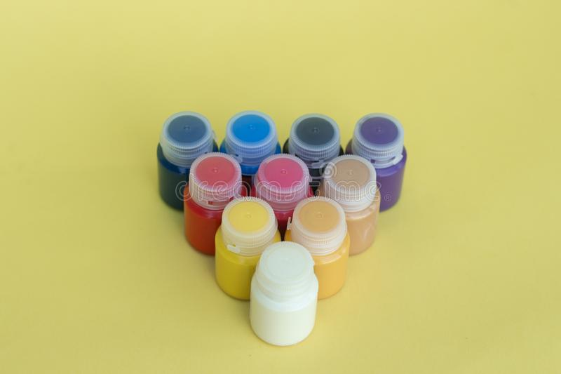 Multicolored plastic cans with acrylic paint on a yellow background. Art supplies. Set for the artist. royalty free stock photography
