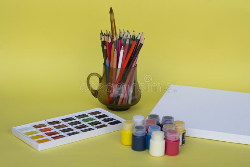 Multicolored plastic cans with acrylic paint on a yellow background. Art supplies. Set for the artist. stock photos