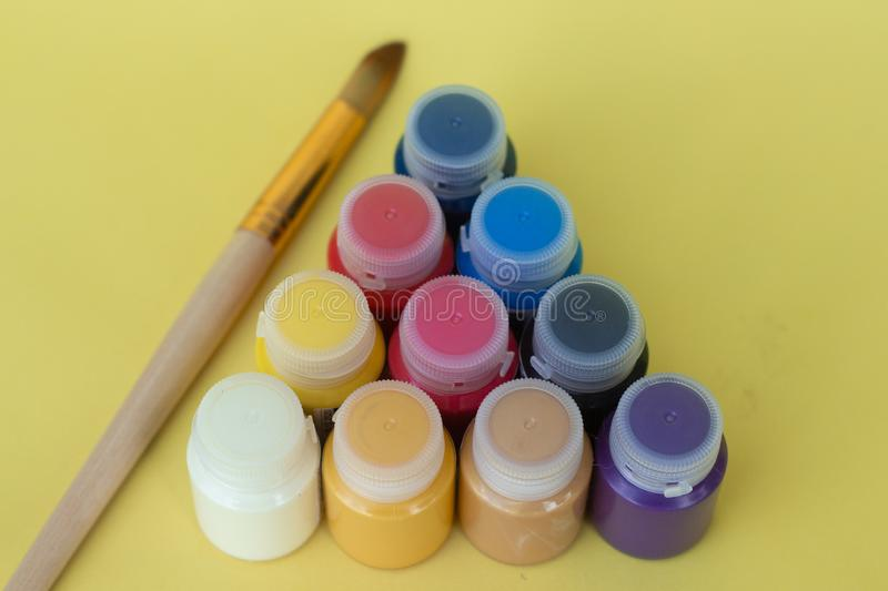 Multicolored plastic cans with acrylic paint on a yellow background. Art supplies. Set for the artist. stock photo