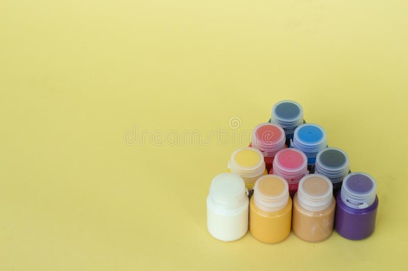 Multicolored plastic cans with acrylic paint on a yellow background. Art supplies. Set for the artist. royalty free stock images