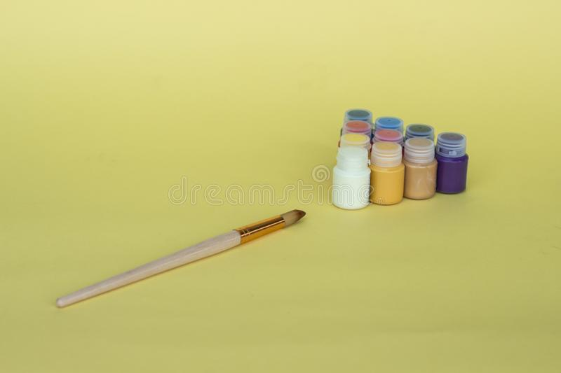 Multicolored plastic cans with acrylic paint on a yellow background. Art supplies. Set for the artist. royalty free stock image