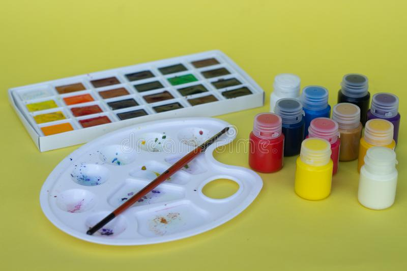 Multicolored plastic cans with acrylic paint on a yellow background. Art supplies. Set for the artist. stock photography
