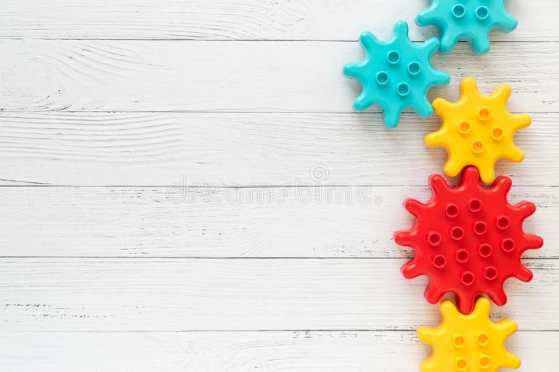 Lego Plastic constructor gearwheels on white wooden background. Popular toys. Copyspace. Lego Multicolored Plastic constructor gearwheels on white wooden royalty free stock photos