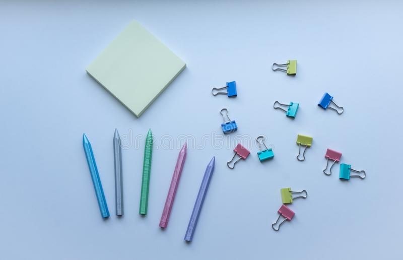Multicolored plastic crayons, paper-clips and yellow sticky note pad from top view on white background. Concept of creativity. Art supplies. Childhood royalty free stock photo
