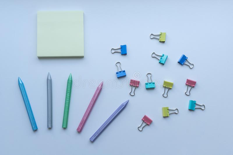 Multicolored plastic crayons, paper-clips and yellow sticky note pad from top view on white background. Concept of creativity. Art supplies. Childhood royalty free stock photos