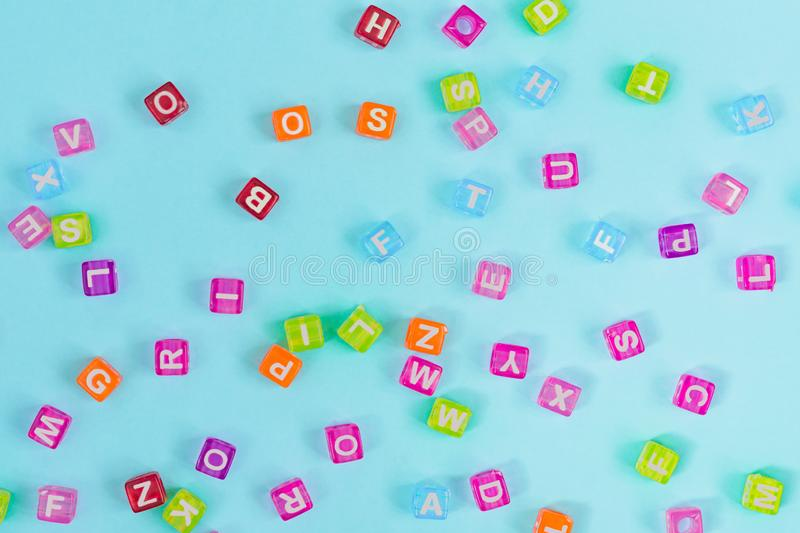 Multicolored plastic cube beads with letters scattered on blue background. Alphabet background texture.  stock photography