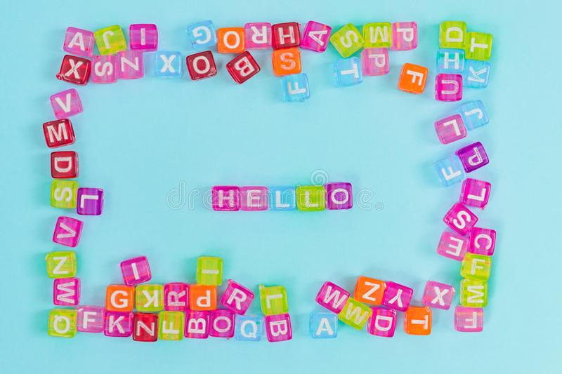 Multicolored plastic cube beads with letters scattered on blue background. English Alphabet background texture. Multicolored plastic cube beads with letters stock photos