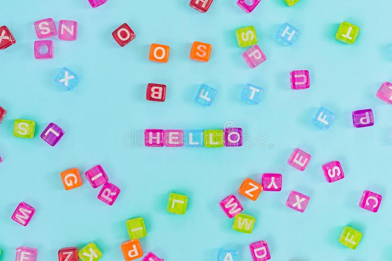 Multicolored plastic cube beads with letters scattered on blue background and words hello. English Alphabet background texture.  royalty free stock image