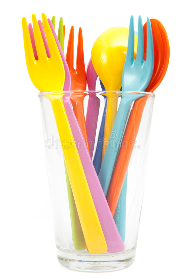 Multicolored plastic forks and spoons on glass royalty free stock images